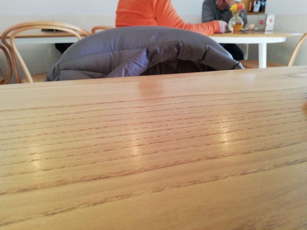 Una coppia anziana che legge e commenta il giornale a un tavolino di un bar.